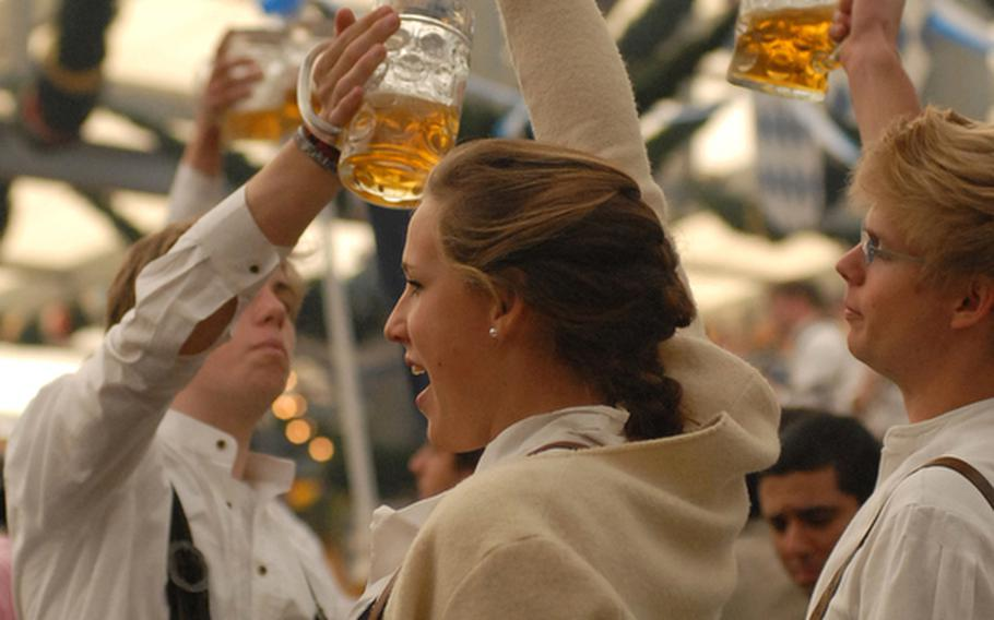 Wearing typical Bavarian dress, friends toast each other.