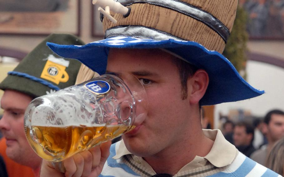They sell funny hats at Oktoberfest, and people actually wear them. This young man probably wished that his keg hat actually held beer.