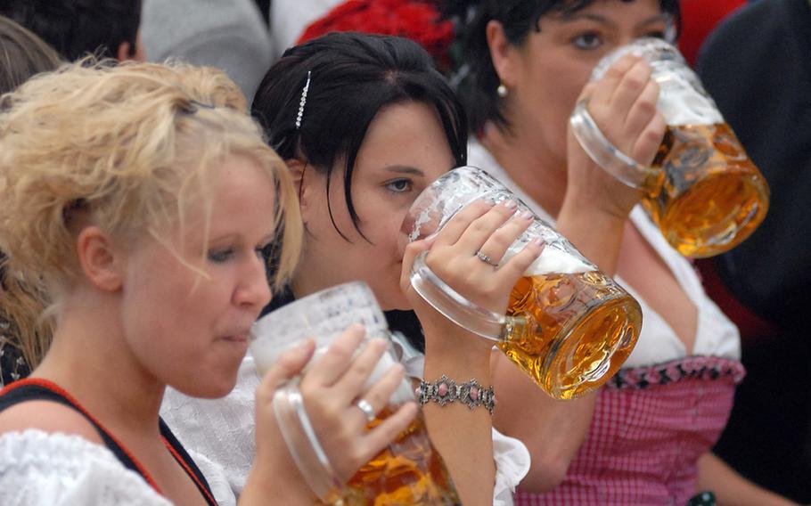 Dirndl-wearing maidens drink from liter mugs in the Ochsenbraterei tent.