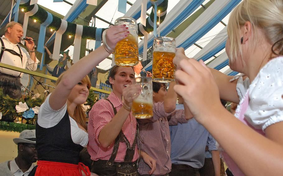 Dressed in typical Bavarian dress, friends toast each other with liter mugs of beer.