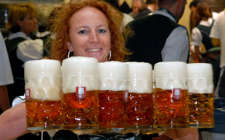 A server heads to the tables with two fistfuls of the one-liter beer mugs that Oktoberfest is famous for.