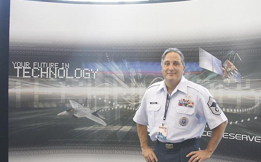 """Chief Master Sgt. Scott H. Terpening poses in front of the Air Force Reserve recruiting booth at PAX Prime in Seattle on Aug. 30. Herpening said of PAX, """"Obviously, we've got dancing zombies. We've got Mario, Sonic the Hedgehogs running around here. That's awesome."""""""