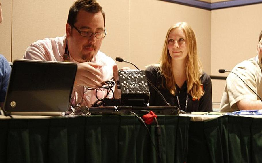 """Mark C. Barlet, left, of the AbleGamers Foundation, unveils what he dubbed a landmark controller for the disabled during panel talk Aug. 30 titled """"Gamers Doing Good."""" On the right is Stefanie Shea, director of Fun For Our Troops, a nonprofit that sends games to troops overseas."""