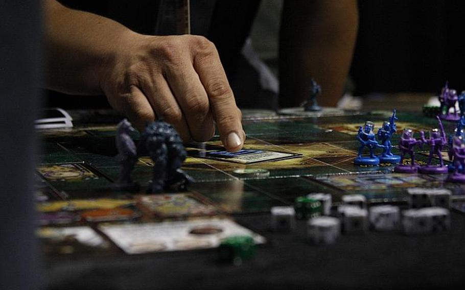 A PAX exhibitor explains a card and figurine game he was showing at the exhibition hall Aug. 30.