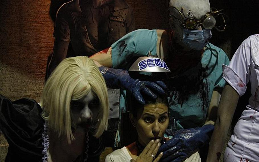 """Gamers lined up to try out """"House of the Dead"""" for the Sony PlayStation's Move controller, and afterward posed for shots with """"House of the Dead"""" zombies."""