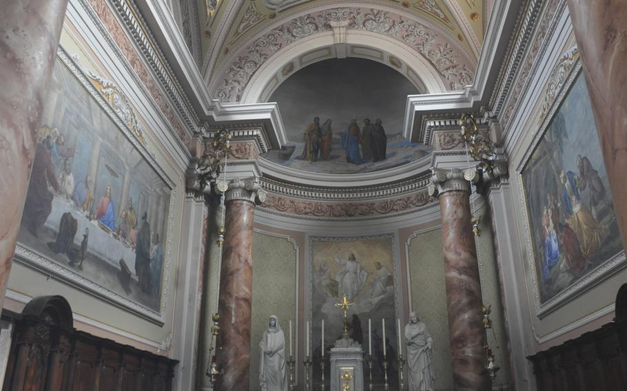 The area surrounding the altar of the parish church in Fagagna features colorful paintings and marbled columns.