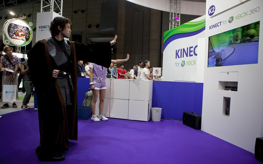 """A truly hardcore Star Wars fan dressed in Jedi attire tests his force push on Microsoft's """"Kinect: Star Wars"""" Saturday at the Tokyo Game Show 2011 held at Chiba Prefecture's Makuhari Messe convention center."""