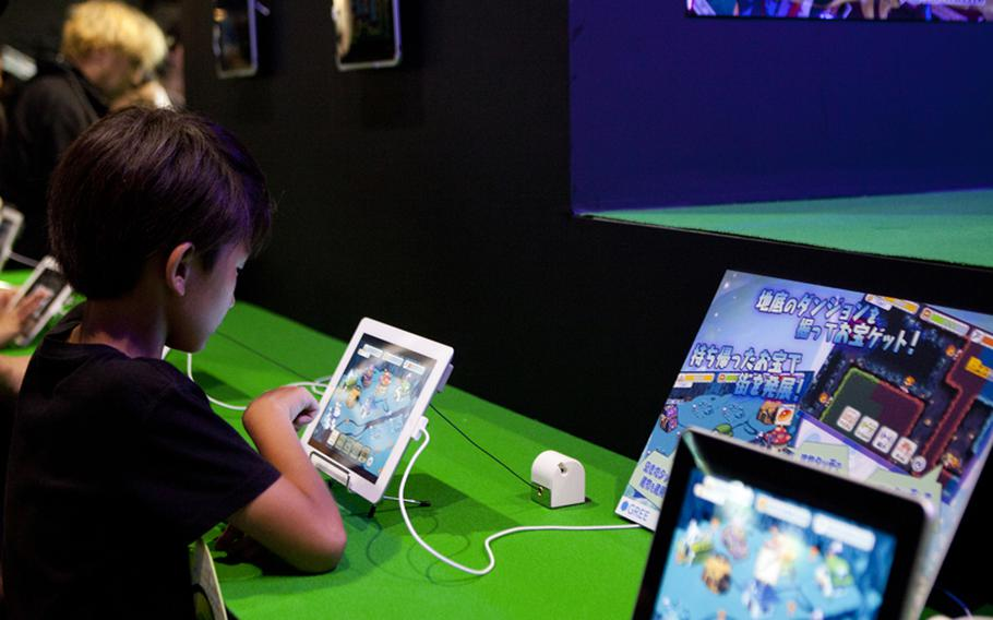 """A young gamer tries out one of the many new titles on display for the Apple iPad, some of the many new titles on display"""" Saturday at this year's Tokyo Game Show held at Chiba Prefecture's Makuhari Messe convention center."""