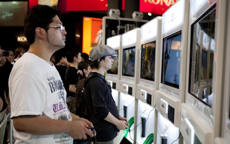 Gamers try out some of the new upcoming games at the Microsoft booth Saturday at the Tokyo Game Show at Chiba Prefecture's Makuhari Messe convention center.