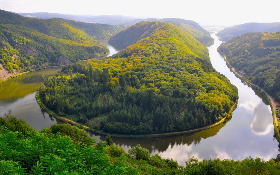 The perfect  view of Saarschleife, a U-shaped bend in the Saar River, near Mettlach, Germany. Benches on a cliff allow visitors to sit and take in the view.