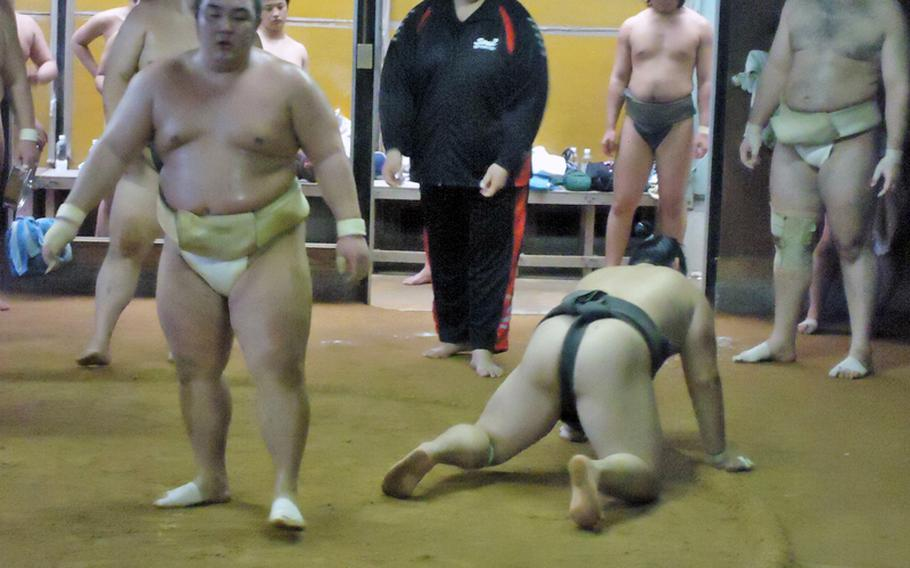 A coach looks on smiling as one wrestler picks himself up out of the dirt and another looks to his next opponent during training at the Sadogatake sumo wrestler stable in Fukuoka recently.