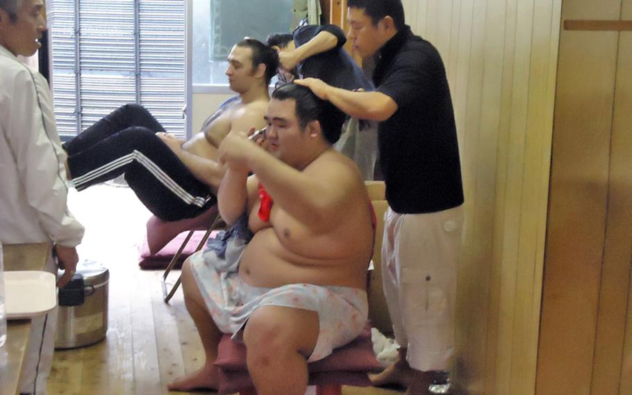 The two famed ozeki Kotooshu, left, and Kotoshogiku, from the Sadogatake sumo wrestler stable in Fukuoka get their hair done after a morning traning session.