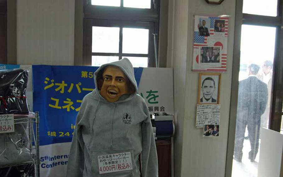 A Halloween mask of President Barack Obama is crudely positioned atop a manequin selling sweatshirts in the tourist information center in Obama. Other memorabilia regarding the president can be seen in the background.