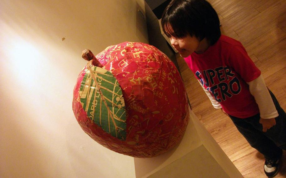 Diego Jimenez looks at a giant apple made entirely of paper during a visit to the Jong IE Nara Paper Art Museum in Seoul.