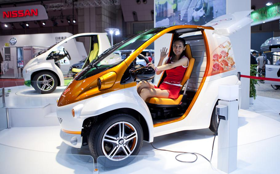 A model waves from Toyota's plugged-in EV COMS concept car.