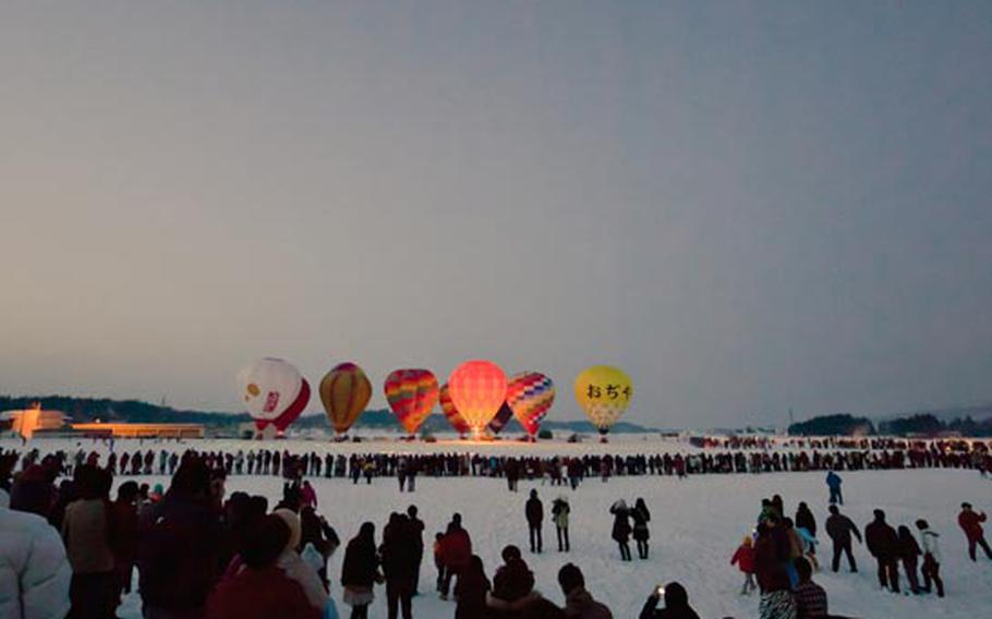 Crowds gather to see the fireworks and hot air balloons during the 2011 hot air balloon festival in Ojiya, Japan.