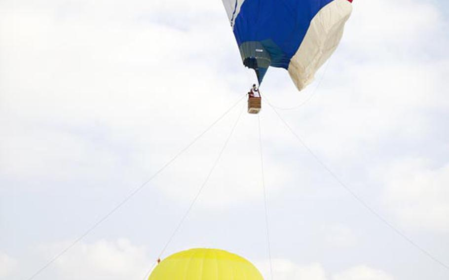 A balloon shaped like Doraemon, a popular Japanese manga character, takes visitors for a ride at the 2011 hot air balloon festival in Ojiya, Japan.