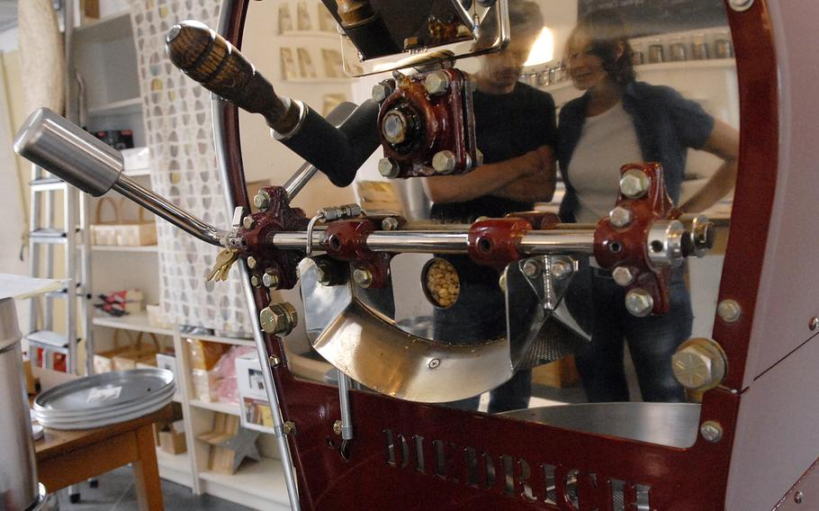 Christian and Stephanie Bebensee, owners of Kaffeerösterei Kaiserslautern, are reflected in the coffee roaster  that stands in a back room of the cafe.