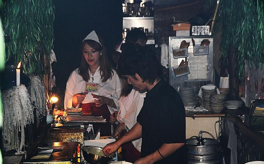 Hell's kitchen: a chef at Yurei prepares a ghost-related dish as waitresses prepare to serve it.