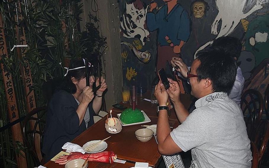 """A birthday girl at Yurei clowns around for a photo after being served her celebratory green """"brain."""""""