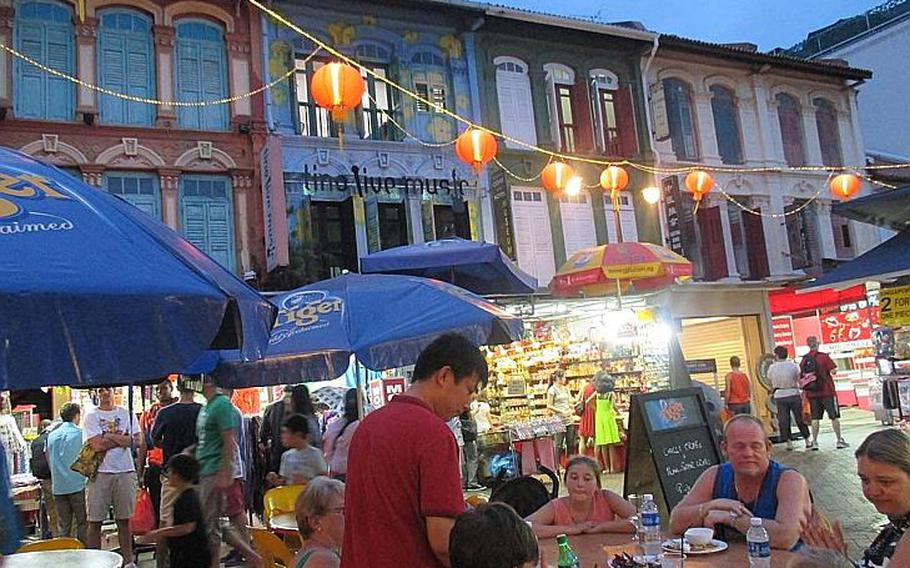 Tourists shop and eat dinner at dusk in Singapore's bustling Chinatown.