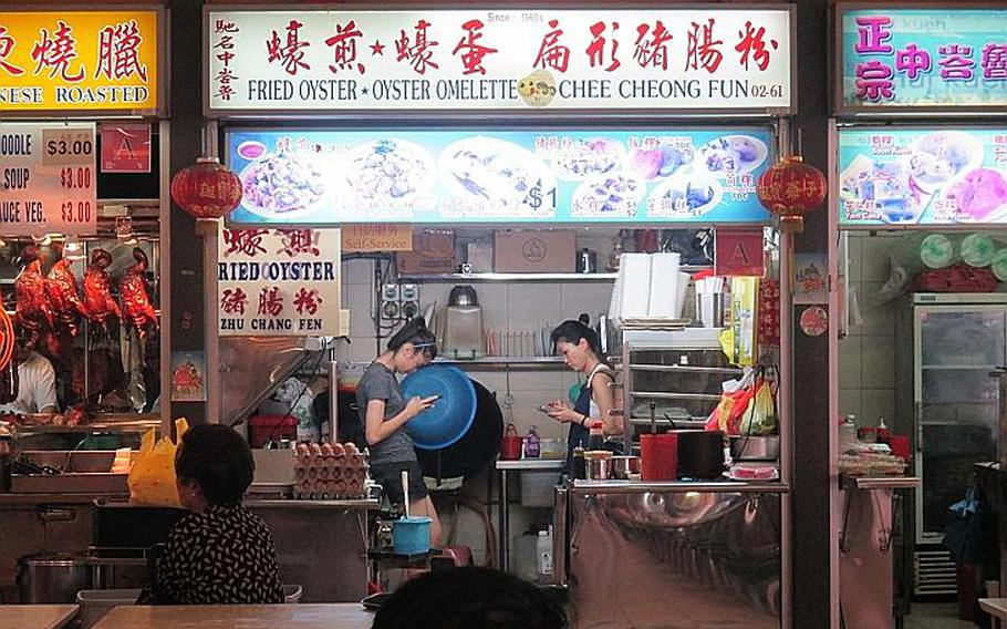 Cooks relax during a lull in business at Singapore's Tiong Bahru food center.