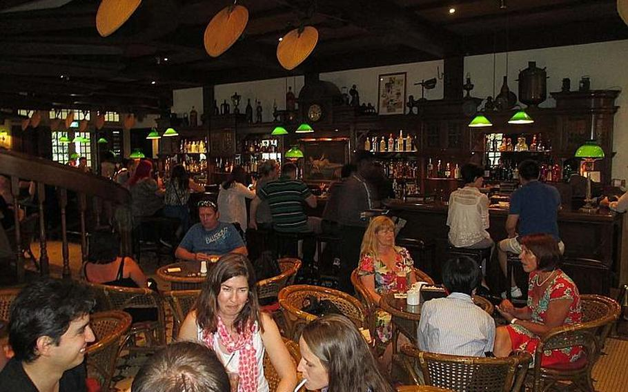 Tourists drink Singapore Slings inside the Long Bar at the Raffles Hotel in Singapore, where the drink was invented.