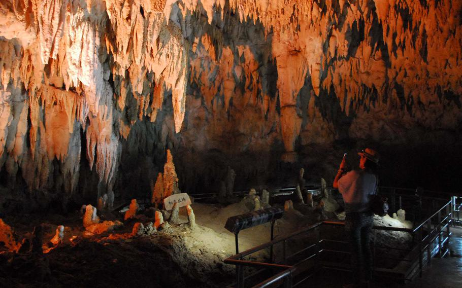 A woman photographs a chamber of stalactites.