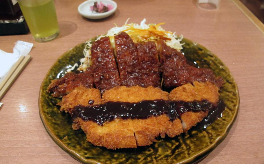 Miso katsu, shown on the upper half of the plate, is a Nagoya specialty. On the opposite site of the plate is a more common version of Japanese deep-fried pork.