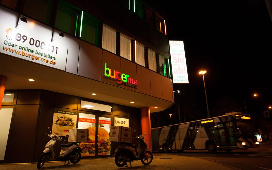 Burgerme scooters sit outside the chain's store in Kaiserslautern waiting to transport hot beef to customers.