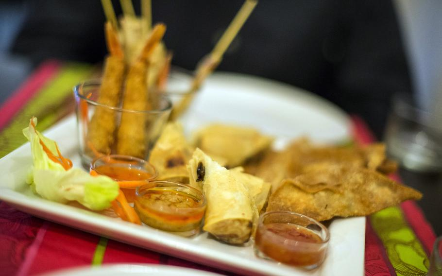 """The appetizer plate at thaicafe in the Chiaia district of downtown Naples, Italy, offers a small mixture of fried spring rolls; meat-filled, fried """"croccantini""""; breaded shrimp; and chicken satay.  Steven Beardsley/Stars and Stripes"""