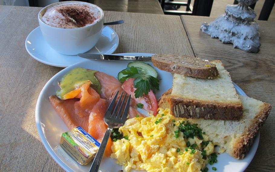 The breakfast menu at Hüftengold, a cafe in downtown Stuttgart, includes scrambled eggs with a variety of sides, such as smoked salmon. The cappuccino is served with a rich cream and melted chocolate.