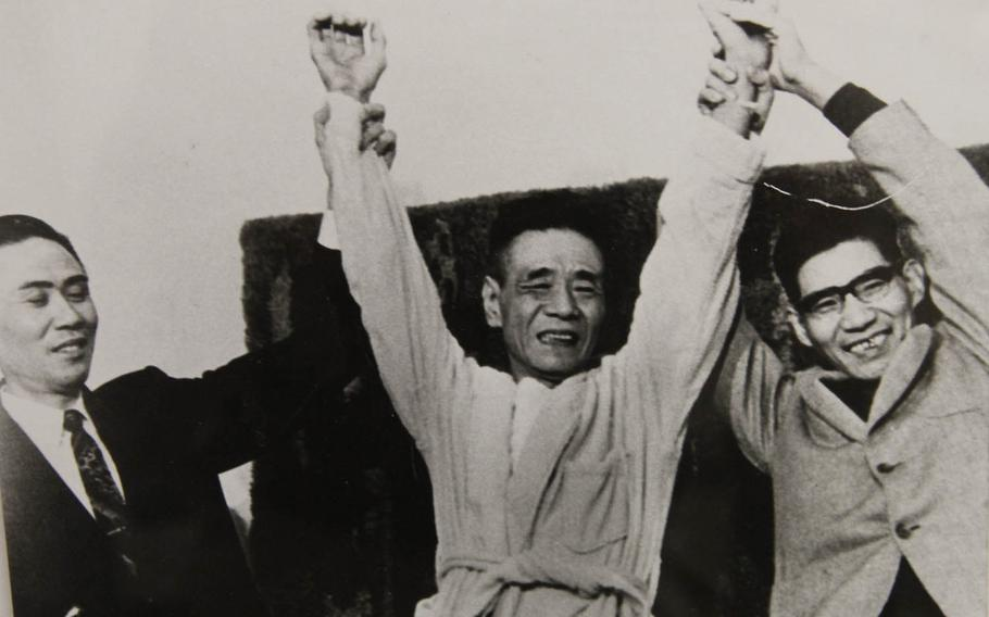 Cpl. Shoichi Yokoi, center, who held out in the remote jungle of Guam for 28 years after the end of World War II, raises his hands with two other former holdouts of the Japanese army on July 30, 1972, in this photo displayed at the Pacific War Museum, Guam.