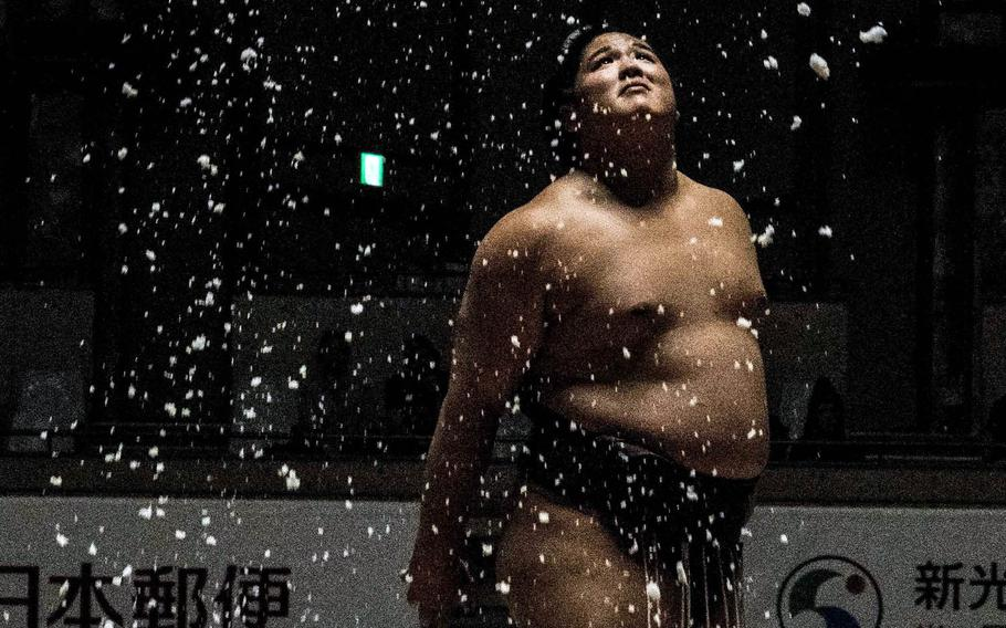 Rikishi sprinkle salt around their bodiesduring a December sumo tournament in Okinawa, Japan.