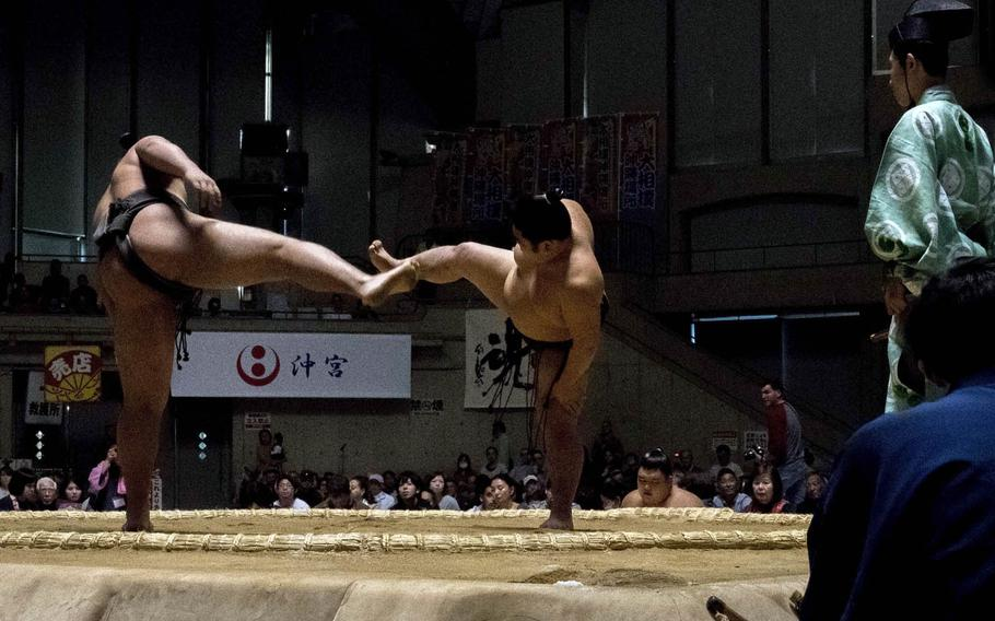 Sumo wrestlers enter the ring, face each other and lift their legs high in the air before stomping them down to scare away demons.