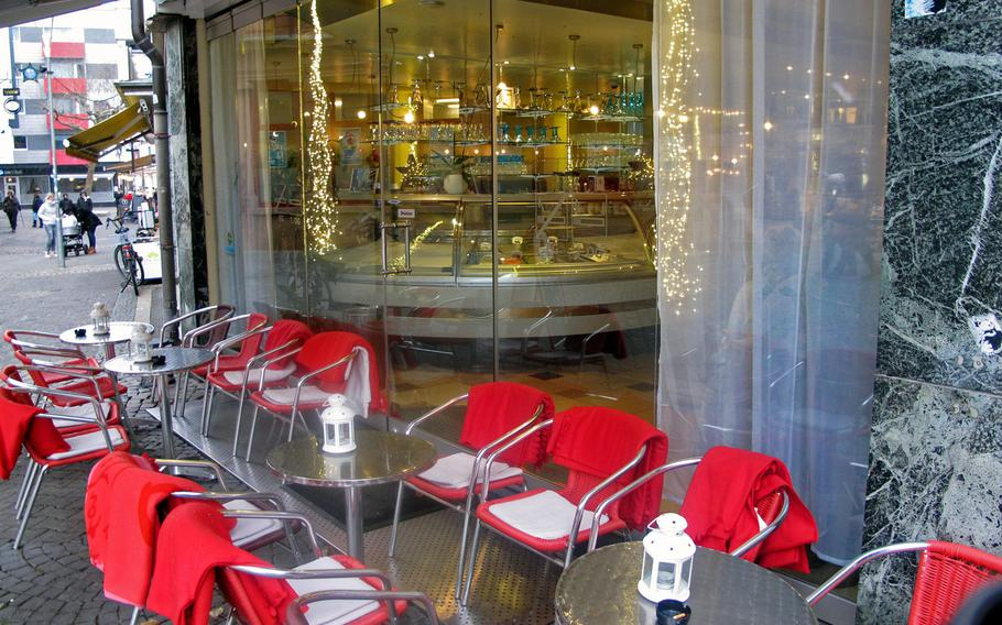 A row of tables and chairs sits outside of Eiscafe Dolomiten on a cold January day in Kaiserslautern, Germany. Visitors to Dolomiten can get a quick takeaway scoop, sit at an outdoor table or lounge in the cafe's warm, luxurious dining area inside.
