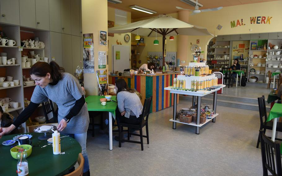 A few customers paint ceramics at Mal-Werk in Mainz, Germany, on a recent weekday morning. On weekends, the paint-your-own pottery shop and cafe is a popular venue for children's birthday parties, and reservations are suggested.