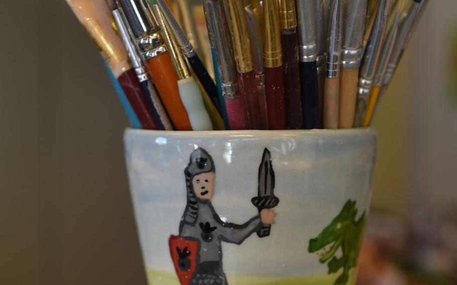 A hand-painted mug holds various paintbrushes at Mal-Werk.