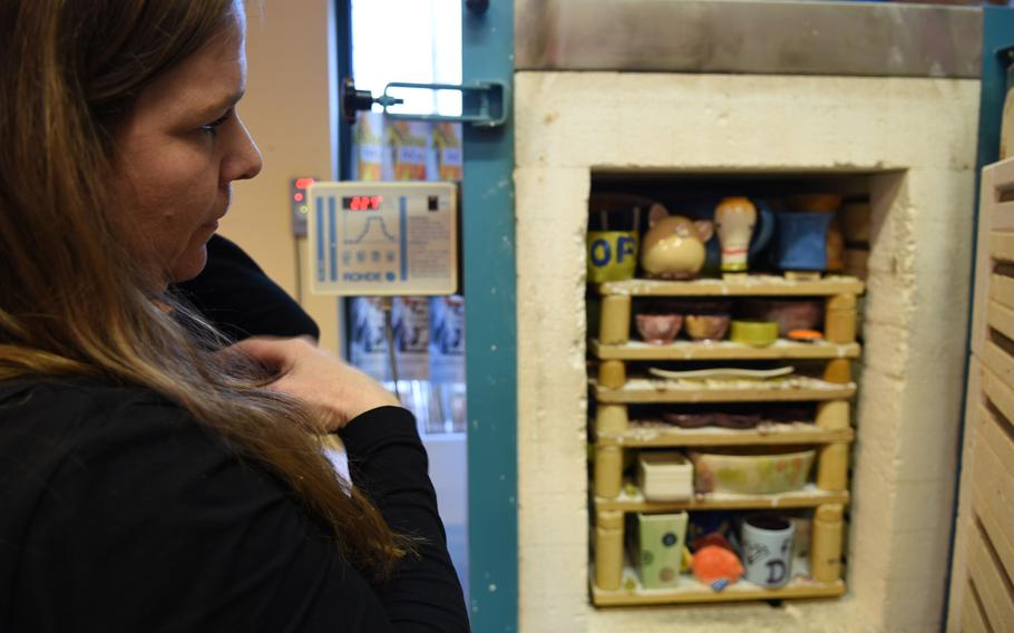 Alexandra Doss, the owner of Mal-Werk, looks inside the shop's kiln, where she fires pieces of pottery hand-painted by customers.