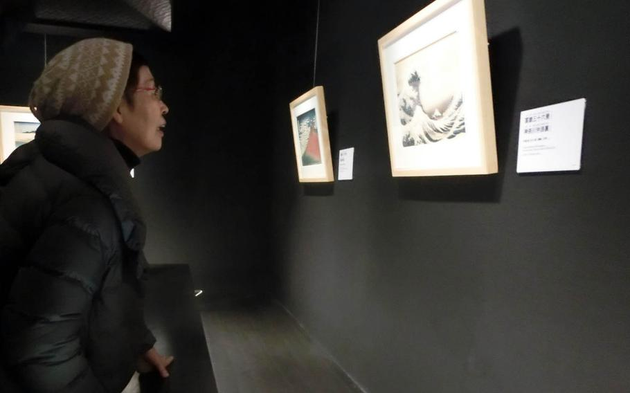A woman takes a close look at replicas of famous paintings by Katsushika Hokusai at the Sumida Hokusai Museum in Tokyo.