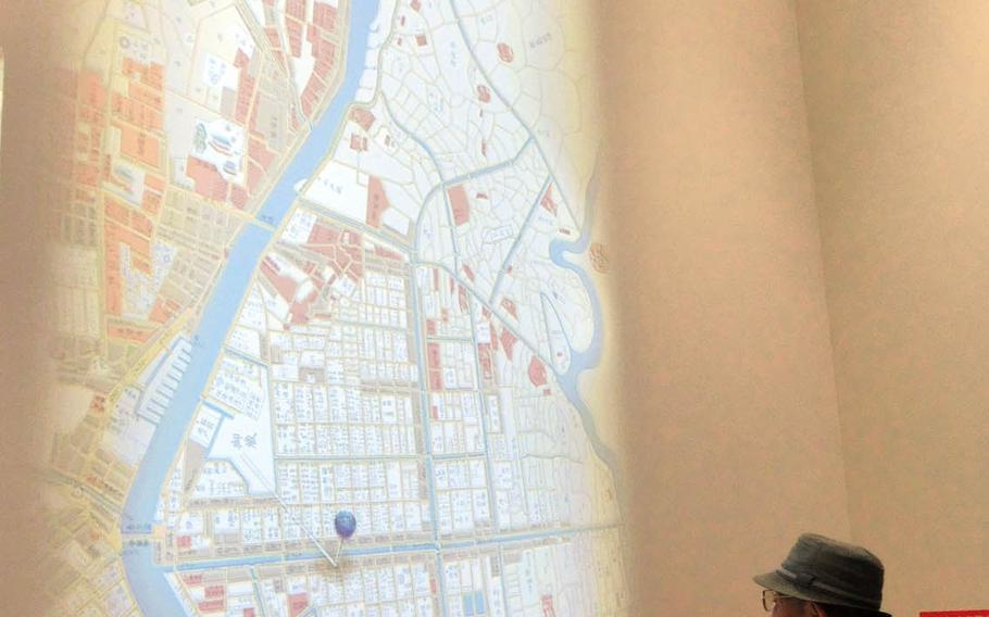 A visitor looks at a map of Sumida city projected on a wall of the Sumida Hokusai Museum in Tokyo. The map shows where some of artist Katsushika Hokusai's works were painted.