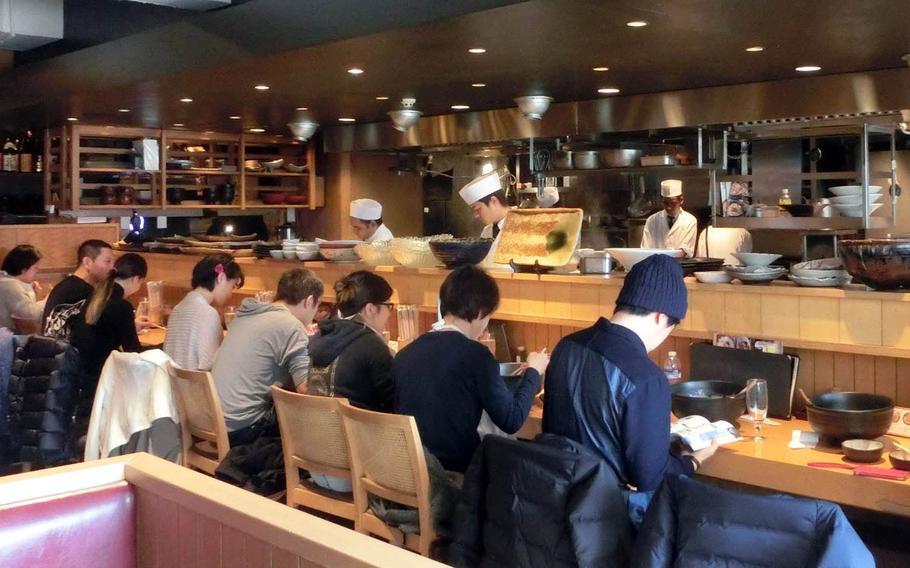 Chefs at Tsuru Ton Tan in Tokyo prepare udon in an open kitchen while customers fill the counter seats.