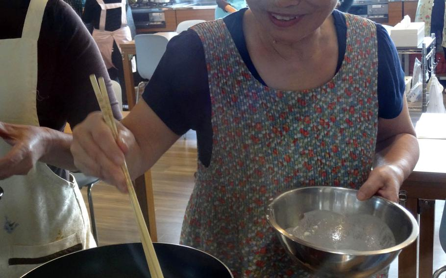 Toshiko Kamiyama is pleased with her success at making kintsuba cakes recently at the Kae Project Cooking School in Yomitan, Okinawa. The cake, made of sweetened purple sweet potatoes, is a Yomitan specialty.
