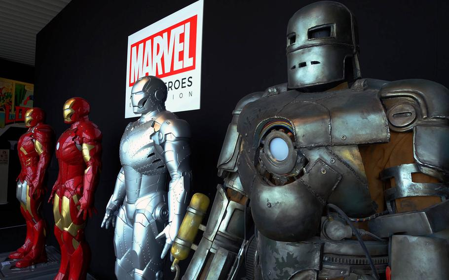 Visitors can pose for a photo with life-size displays of various Iron Man suits from over the past few decades at Marvel's Age of Heroes exhibit in Tokyo.