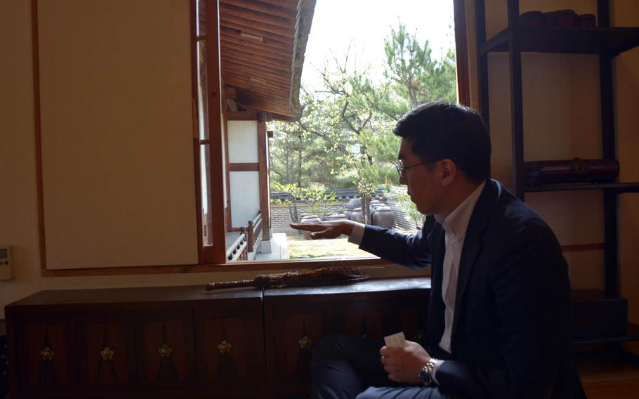 Joshua Park, director of strategic planning at the Korea Furniture Museum in Seoul, demonstrates how furniture was built to fit traditional houses at a low level to allow people sitting on the floor to easily look outside and enjoy nature.