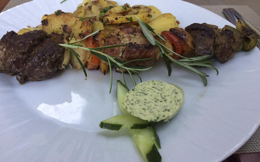 """A """"Viking skewer"""" one of the house specialties at Weber's Wikinger in Wiesbaden's old city. Lamb, beef and pork medallions with peppers and onions on a skewer, along with roasted potatoes and herb butter."""
