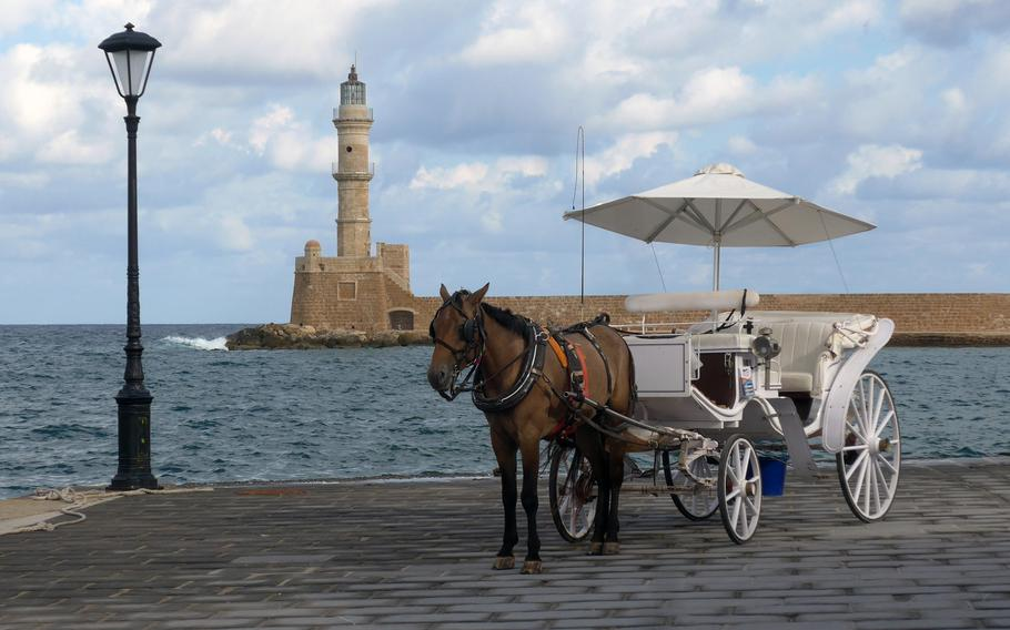 A horse and buggy stands on the Chania Crete's Old Harbor promenade. In the background is the Venetian Lighthouse
