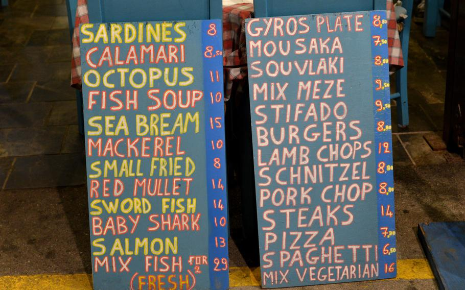 Signs announce what a Chania, Crete, restaurant has to offer. For the tourist, Chania is a great place to sample Greek and Cretan cuisine.