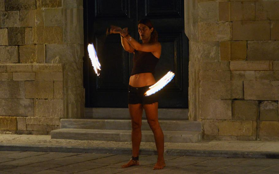 A street performer entertains tourists in Chania, Crete with a fiery performance.