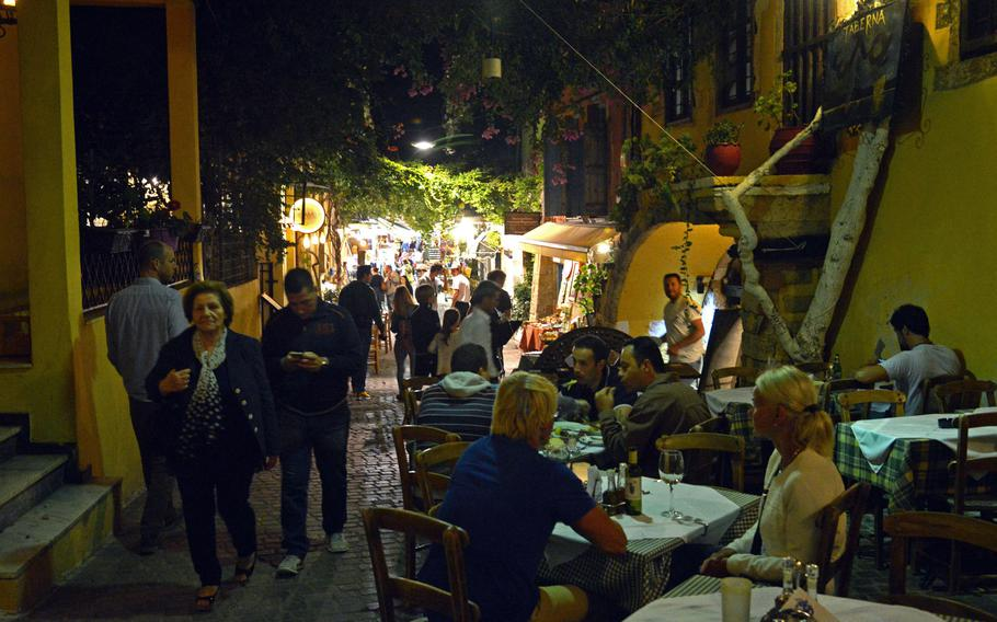 People enjoy a Cretan dinner as others wander along the shop-lined cobblestone alleys in Chania, Crete.